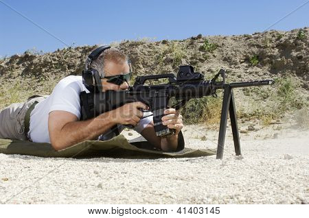 Side view of a man in shooting position on shooting range