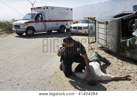 Police officer checking pulse of car crash victim
