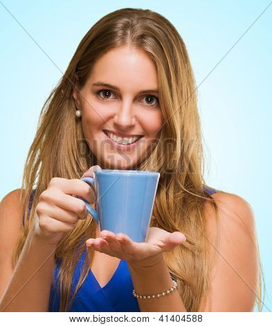 Smiling Woman Holding Cup against a blue background