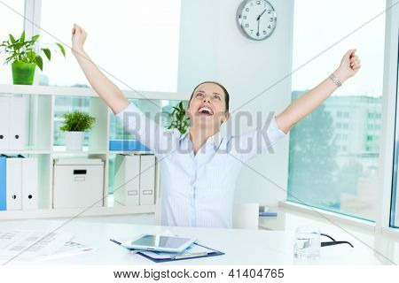 Portrait of excited businesswoman raising arms in office