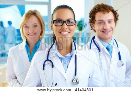 Portrait of three clinicians in white coats looking at camera with smiling brunette in front