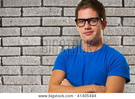 Handsome young man wearing eyeglasses against a brick wall