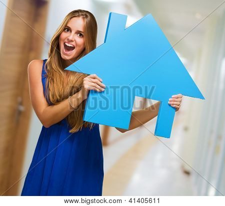 Portrait Of A Young Woman Holding A Haus Modell in einer Passage Weg