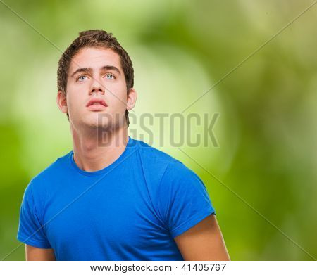 Handsome young man looking up against a nature background