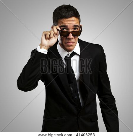 portrait of business man taking off the sunglasses against a grey background