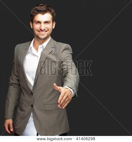 Portrait Of  Young Businessman In A Suit Holds Out His Hand For A Handshake On Black Background