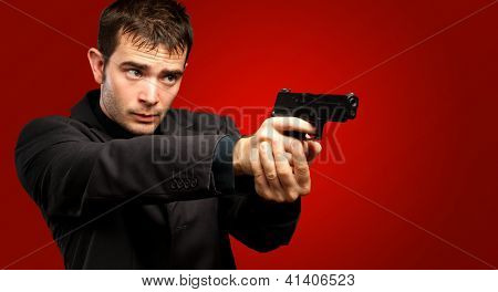 Man Holding Gun against a red background