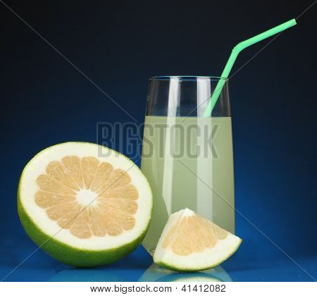 Delicious sweetie juice in glass and sweetie next to it on dark blue background
