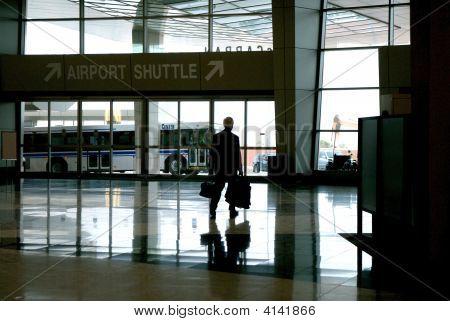 Business-Mann zu Fuß aus dem Flughafen