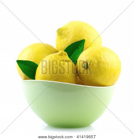 fresh lemon in green bowl isolated on white