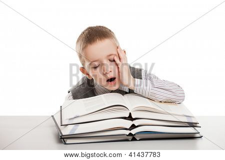 Tired child boy yawning on education reading books at school desk