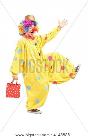 Full length portrait of a happy clown holding a bag and walking isolated on white background