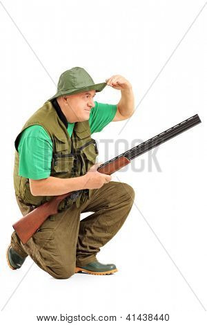 Hunter with rifle crouching and looking in the distance isolated on white background