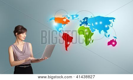 Beautiful young woman holding a laptop and presenting colorful world map