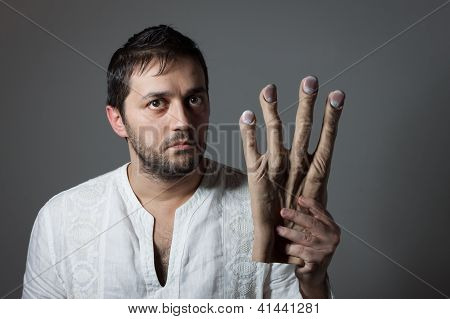 Young Bearded Man Holding A Huge Mock Hand