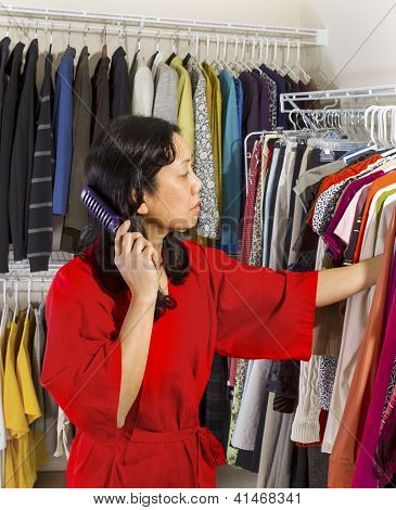 Mature Woman Combing Hair While In Closet