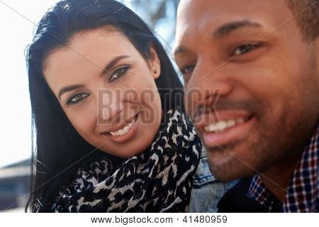 Outdoor portrait of young couple. Focus on woman looking to man, smiling.