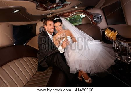 Romantic young couple sitting in limo on wedding-day, clinking glasses.