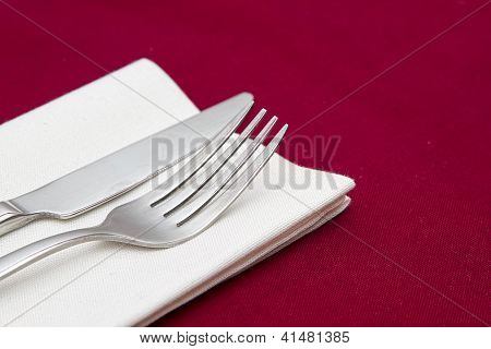 Knife and fork with white napkin