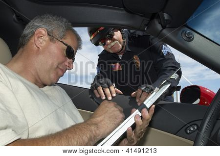 Mature police officer looking at man in car signing papers
