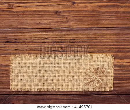 Sackcloth Tag Over Brown Wooden Board Background