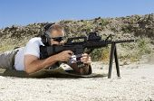 stock photo of shooting-range  - Side view of a man in shooting position on shooting range - JPG