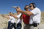 stock photo of shooting-range  - Lieutenant standing with troops holding guns on training - JPG