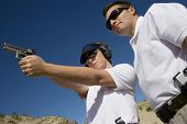 picture of handgun  - Trainer helping young woman to aim with handgun at combat training - JPG