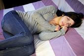 stock photo of sorrow  - Depressed young woman in bed after domestic violence at home - JPG