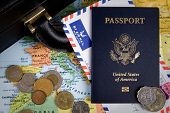 stock photo of american money  - USA passport foreign coins and briefcase sit on a world map for an international business travel concept - JPG
