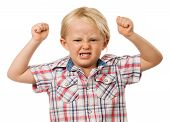 pic of misbehaving  - A frustrated and angry young boy with fists raised in the air and pulling a face - JPG