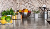 stock photo of granite  - Modern kitchen countertop with food ingredients and green herbs - JPG