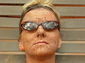 foto of mud pack  - woman wears her sunglasses while getting a mud facial - JPG