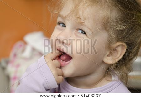 The little girl fervently looks in a shot, having thrust a finger into a mouth