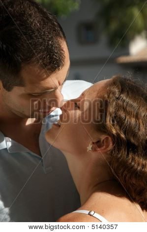 Close Up Of Beautiful Couple Smiling About To Kiss Outside