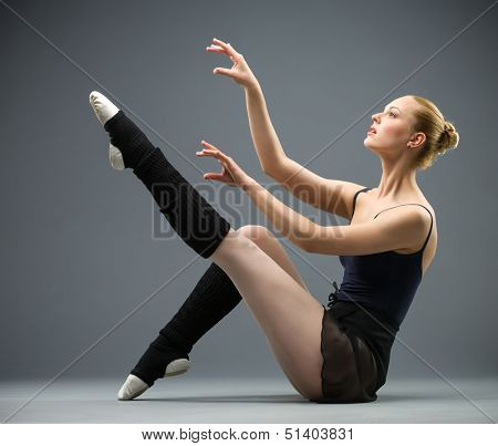 Sideview of dancing on the floor ballerina with her leg up, isolated on grey. Concept of elegant art and sportive hobby