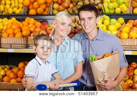 Happy family against shelves of fruits goes shopping. Father keeps a paper bag with fruits and son sits in the cart