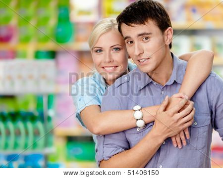 Girl embraces man in the shopping center. Concept of happy relationship and affection