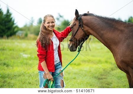 Beautiful smiling girl with her brown horse outdoors