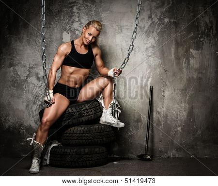 Beautiful muscular bodybuilder woman sitting on tyres and holding chains