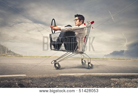businessman driving with a shopping cart on the road