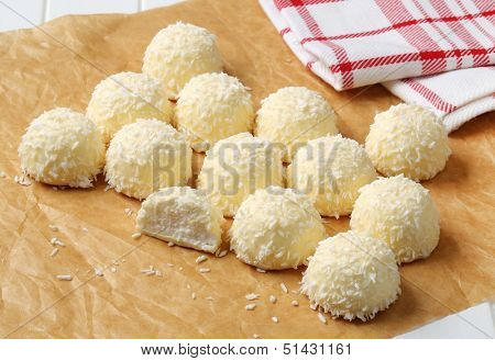 white chocolate bonbons with coconut, on a baking paper