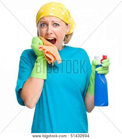 Young woman - cleaning maid with rag and sprayer holding her face in astonishment, isolated over white