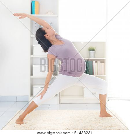 Prenatal yoga class. Full length healthy 8 months pregnant calm Asian woman meditating or doing yoga exercise at home. Relaxation and stretching.