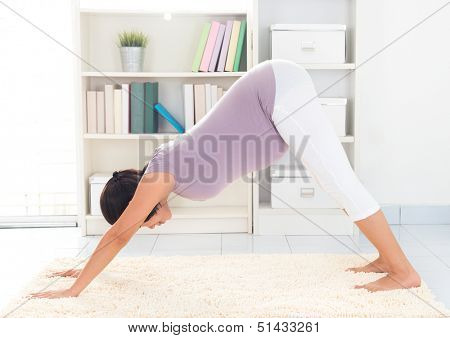 Prenatal yoga meditation. Full length healthy 8 months pregnant calm Asian woman meditating or doing yoga exercise at home. Relaxation yoga facing downward dog positions.
