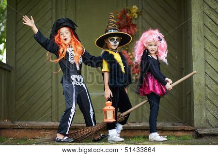 Portrait of three Halloween girls with broom looking at camera outside