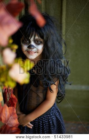 Portrait of spooky girl in Halloween attire looking at camera