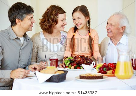 Portrait of happy family sitting at festive table and having Thanksgiving dinner