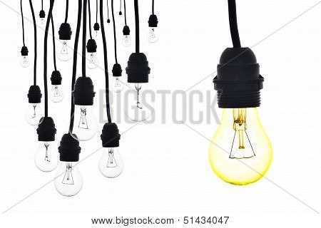 A Yellow Light Bulb Hanging Next To A Number Of Lamps