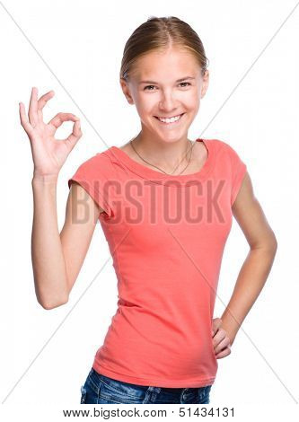 Young teen girl is showing OK sign, isolated over white